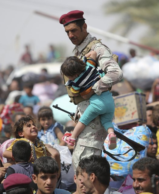 An Iraqi soldier carries a child as displaced Sunni people, who fled the violence in the city of Ramadi, arrive at the outskirts of Baghdad, April 17, 2015. (Photo by Reuters/Stringer)