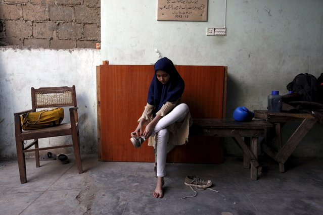Tabia, 12, removes her shoes after finishing an exercise session at the first women's boxing coaching camp in Karachi, Pakistan February 19, 2016. (Photo by Akhtar Soomro/Reuters)