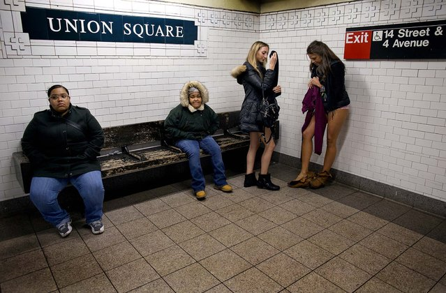 Leah Estreicher and Marianne Cornejo start to get dressed at the Union Square subway station after participating in the annual No Pants Subway Ride in New York. (Photo by Craig Ruttle/Associated Press)