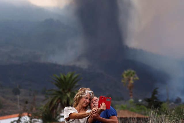 A couple takes a selfie in front of the erupting volcano, in Los Llanos de Aridane on the Canary Island of La Palma, Spain on September 20, 2021. (Photo by Nacho Doce/Reuters)