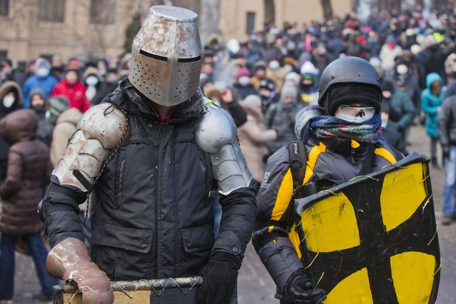 Protesters clad in improvised protective gear prepare for a clash with police in central Kiev, Ukraine, Monday, January 20, 2014. After a night of vicious streets battles, anti-government protesters and police clashed anew Monday in the Ukrainian capital Kiev. (Photo by Evgeny Feldman/AP Photo)