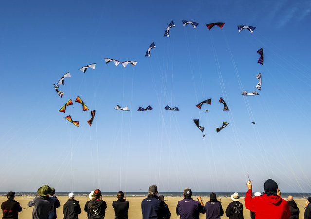 "People fly their kites to form the shape of a car in the sky on the beach in Berck, northern France, on April 20, 2015, during the 29th ""Rencontres Internationales de Cerfs Volants"" (International Kite Meeting) which runs from April 18 to 26. (Photo by Philippe Huguen/AFP Photo)"