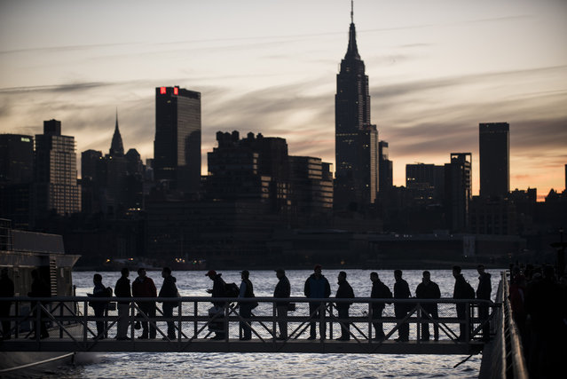 People board the NY Waterways ferry with the Manhattan skyline in the background November 1, 2012 in Hoboken, New Jersey. (Photo by Brendan Smialowski/AFP Photo)