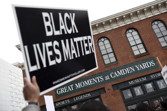 Demonstrators gather near Camden Yards to protest against the death in police custody of Freddie Gray in Baltimore April 25, 2015. At least 2,000 people protesting the unexplained death Gray, 25, while in police custody marched through downtown Baltimore on Saturday, pausing at one point to confront officers in front of Camden Yards, home of the Orioles baseball team. (Photo by Sait Serkan Gurbuz/Reuters)