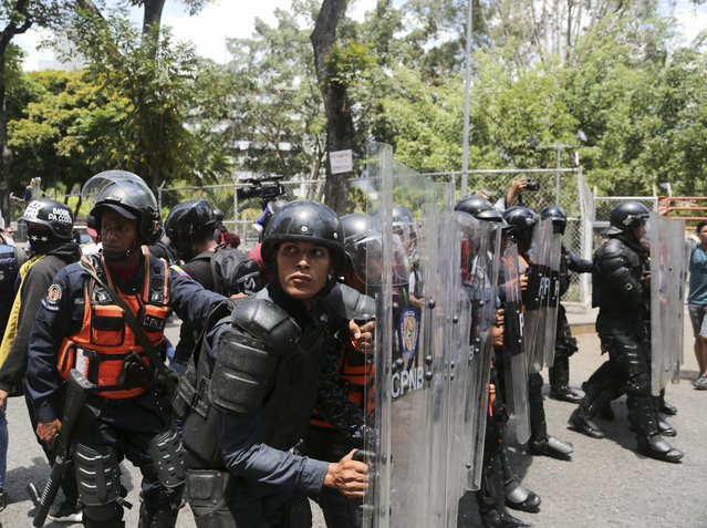 A cordon of Venezuelan National Police officers retreat when confronted by demonstrators who were temporarily blocked by police from getting to a rally against the government of President Nicolas Maduro in Caracas, Venezuela, Saturday, March 9, 2019. (Photo by Fernando Llano/AP Photo)