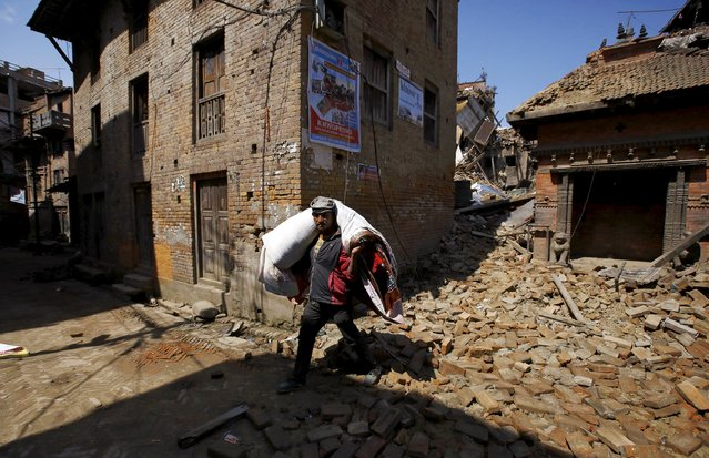A man carrying bedding walks past rubble of collapsed houses following Saturday's earthquake in Bhaktapur, Nepal April 27, 2015. (Photo by Navesh Chitrakar/Reuters)