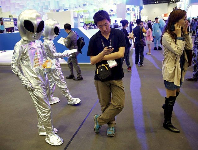 Visitors use mobile phones next to promotional staff in alien outfits at the Global Mobile Internet Conference (GMIC) 2015 in Beijing, China, April 28, 2015. (Photo by Kim Kyung-Hoon/Reuters)