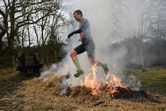 """A competitor jumps a burning bale of hay as he takes part in the """"Tough Guy"""" adventure race near Wolverhampton, central England, on January 29, 2017. (Photo by Oli Scarff/AFP Photo)"""