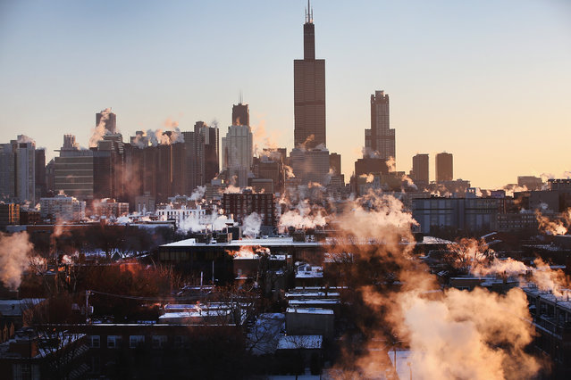 The sun rises behind the skyline as temperatures hovered around -10 degrees January 28, 2014 in Chicago, Illinois. (Photo by Scott Olson/Getty Images)
