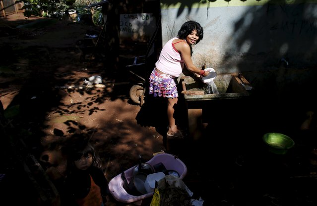 A Guarani Indian pregnant woman washes a set of kitchen pots and pans as she looks at her daughter in the village of Pyau at Jaragua district, in Sao Paulo April 28, 2015. More than 700 Guarani Indians live in three villages in the Jaragua district in Sao Paulo. (Photo by Nacho Doce/Reuters)