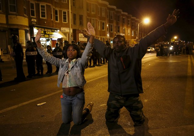 People gesture while kneeling along Pennsylvania Avenue, past the curfew, two days after it was looted and set ablaze in protest against the death of Freddie Gray, a 25-year-old black man who died in police custody, in Baltimore, Maryland April 29, 2015. (Photo by Shannon Stapleton/Reuters)