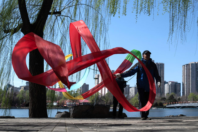 A man draws circles with a ribbon in Yuyuantan park in Beijing on March 21, 2019. (Photo by Fred Dufour/AFP Photo)