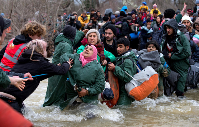 Migrants cross a river after leaving the Idomeni refugee camp on March 14, 2016 in Idomeni, Greece. The decision by Macedonia to close its border to migrants on Wednesday has left thousands of people stranded at the Greek transit camp. The closure, following the lead taken by neighbouring countries, has effectively sealed the so-called western Balkan route, the main migration route that has been used by hundreds of thousands of migrants to reach countries in western Europe such as Germany.  (Photo by Matt Cardy/Getty Images)