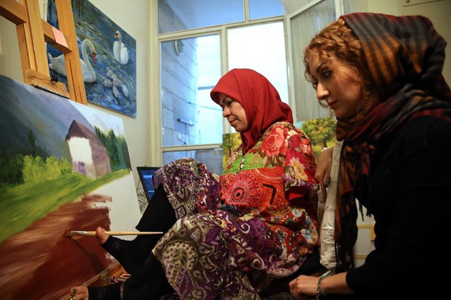 """In this picture taken on Wednesday, January 28, 2015, Zohreh Etezadossaltaneh, left, who was born without arms, paints as her teacher Parisa Samavatian observes, at her home in Tehran, Iran. """"She works so easily that I've totally forgotten she paints with her feet"""", said Samavatian. (Photo by Ebrahim Noroozi/AP Photo)"""