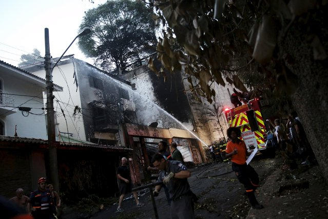 Firefighters try to extinguish a fire where a small airplane crashed into the house in São Paulo, Brazil, March 19, 2016. A small plane owned by the former chief executive of mining giant Vale has crashed into a residential area near an airport in the Brazilian city of São Paulo, killing the businessman and six others, local officials say. One person on the ground was also injured. The accident happened at around 3:30 p.m. local time on Saturday when the plane, believed to be a Comp Air 9 aircraft, went down at the edges of a neighborhood in Case Verde district, just outside Campo de Marte Airport in São Paulo. (Photo by Nacho Doce/Reuters)