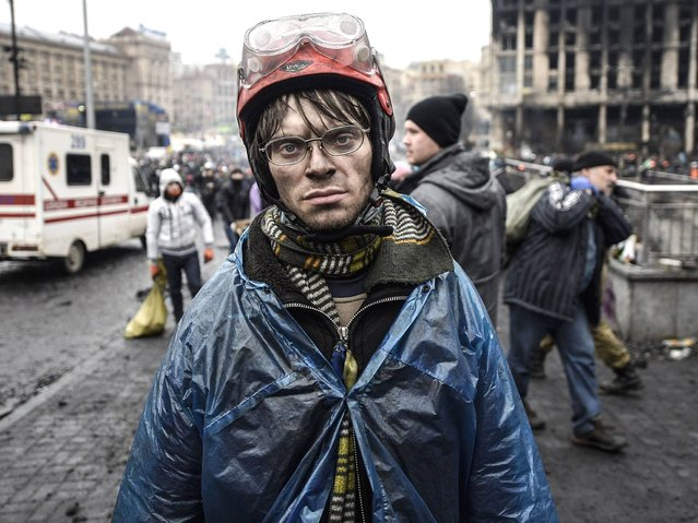 A protestor carries food for demonstrators on the barricades during the face off against heavily-armed police in Kiev, on February 20, 2014. (Photo by Bulent Kilic/AFP Photo)