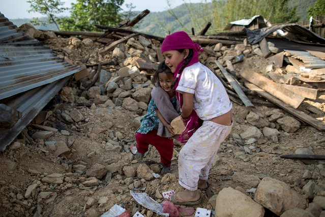 Reshmila, 8, (R) and Shamjana, 5, throw debris as they play at the site of their collapsed house after an earthquake in a village in Sindhupalchowk, Nepal, May 2, 2015. (Photo by Danish Siddiqui/Reuters)