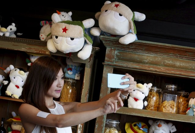 A model poses for a selfie with the newly launched Xiaomi Mi 4i phone in Hong Kong, China May 5, 2015. According to researcher Strategy Analytics, Chinese brand Xiaomi Inc topped the league table in the first quarter of 2015 in China's smartphone market, with 12.8 percent of the 110 million units shipped, followed closely by Apple Inc at 12.3 percent and Huawei Technologies Co Ltd, another Chinese player, at 10.2 percent. (Photo by Bobby Yip/Reuters)