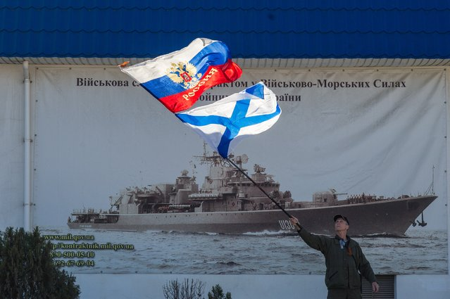 A pro-Russian activist waves the Russian state, upper, and Russian Navy flags outside an entrance to the General Staff Headquarters of the Ukrainian Navy in Sevastopol, Ukraine, Monday, March 3, 2014. Pro-Russian soldiers seem to further cement their control over the strategic region – that also houses the Russian Black Sea Fleet – by seizing a ferry terminal in the Ukrainian city of Kerch about 20 kilometers (12 miles) by boat to Russia, intensifying fears that Moscow will send even more troops into the peninsula. (Photo by Andrew Lubimov/AP Photo)