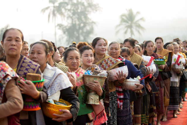 Women line up for alms offering as they take part in an elephant festival, which organisers say aims to raise awareness about elephants, in Sayaboury province, Laos February 17, 2017. (Photo by Phoonsab Thevongsa/Reuters)