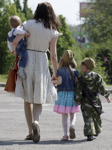 A woman and children attend the so-called parade of children's troops in Rostov-on-Don, southern Russia, May 14, 2015. (Photo by Eduard Korniyenko/Reuters)