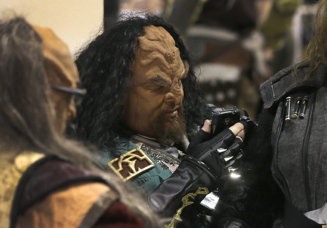Scott Roth, dressed as a Klingon, checks his phone during a break at the Motor City Comic Con at the Suburban Collection Showcase, Friday, May 15, 2015, in Novi, Mich. (Photo by Carlos Osorio/AP Photo)