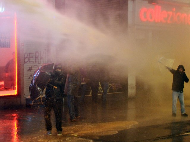 A demonstrator opens his umbrella as police uses a water cannon during clashes between protesters and riot police at Istiklal avenue in Istanbul. (Photo by Ozan Kose/AFP Photo)