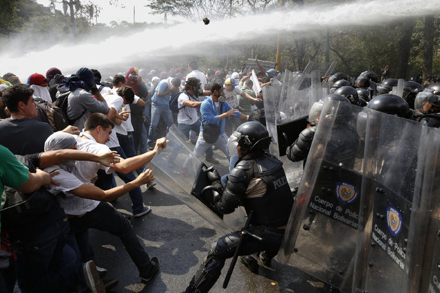 "Anti-government protesters clash with police during a protest in Caracas March 12, 2014. Supporters and foes of Venezuelan President Nicolas Maduro took to the streets of Caracas again on Wednesday a month after similar rival rallies brought the first bloodshed in a wave of unrest round the OPEC member nation. Red-clad sympathizers of Maduro's socialist government held a ""march for peace"" while opponents wearing white gathered to denounce alleged brutality by security forces during Venezuela's worst political troubles for a decade. (Photo by Carlos Garcia Rawlins/Reuters)"