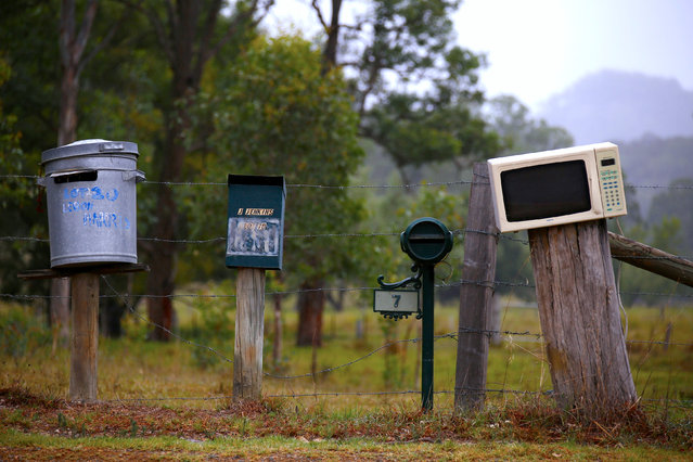 An old microwave and garbage bin, both of which are being used as mailboxes, are seen next to more traditional mailboxes along a road on the outskirts of the township of Wollombi, located north of Sydney, Australia, February 25, 2017. (Photo by David Gray/Reuters)
