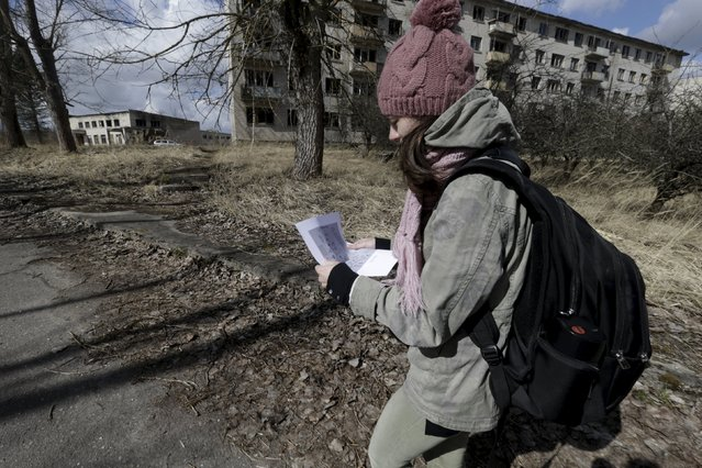 A woman looks at a map as she visits the ghost town of a former Soviet military radar station near Skrunda, Latvia, April 9, 2016. (Photo by Ints Kalnins/Reuters)