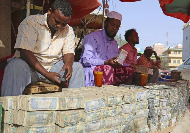 Money changers wait for customers at a local bureau where $100 U.S. dollars exchange for 750,000 Somaliland shillings in Hargeysa, Somalia May 19, 2015. (Photo by Feisal Omar/Reuters)