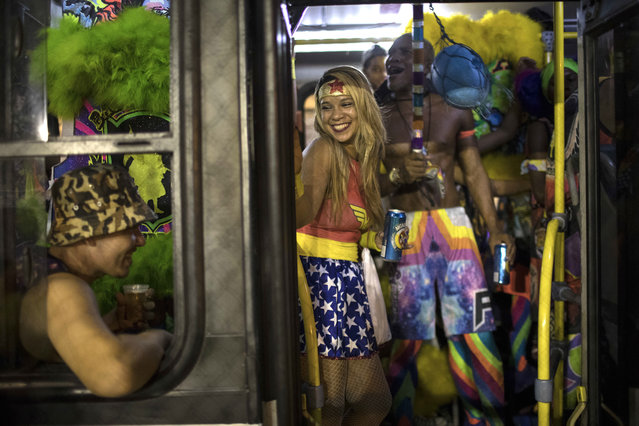 """Revelers wearing costumes pack a bus during carnival festivities in the Cidade de Deus, or """"City of God"""" slum, before going to another party in Rio de Janeiro, Brazil, Monday, February 27, 2017. (Photo by Felipe Dana/AP Photo)"""