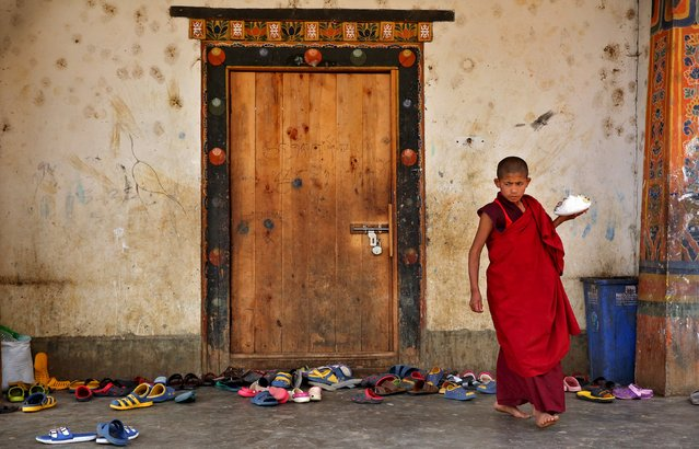 A young monk takes his food from the dining hall at Changangkha Lhakhang temple in Thimphu, Bhutan, April 13, 2016. (Photo by Cathal McNaughton/Reuters)