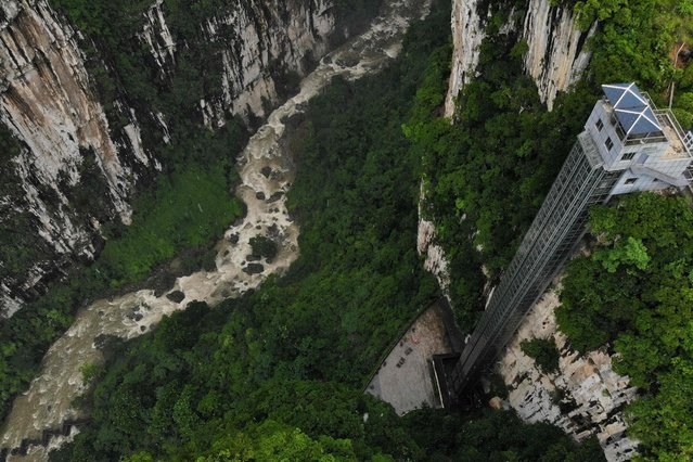 This aerial photo taken on June 18, 2019 shows the Zhijin Grand Canyon sightseeing elevator in Bijie, in southwest China's Guizhou Province. The 108 meter high elevator, which connects the upper and lower levels of the canyon, went into service in 2014. (Photo by AFP Photo/China Stringer Network)