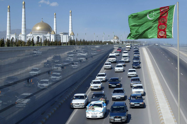 A wedding convoy passes a Turkmen flag near the mausoleum of the country's former leader Saparmurat Niyazov near Ashgabat February 19, 2009. (Photo by Reuters/Stringer)