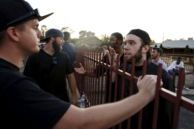 """Members of the Islamic Community Center, including Ilyas Wadood (right), talk with people attending the """"Freedom of Speech Rally Round II"""" outside the center in Phoenix, Arizona May 29, 2015. More than 200 protesters, some armed, berated Islam and its Prophet Mohammed outside an Arizona mosque on Friday in a provocative protest that was denounced by counterprotesters shouting """"Go home, Nazis,"""" weeks after an anti-Muslim event in Texas came under attack by two gunmen.  REUTERS/Nancy Wiechec"""