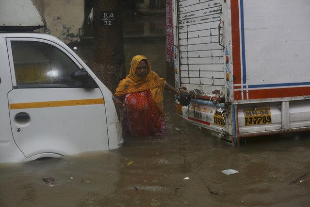 A woman tries to cross through a waterlogged street during monsoon rains in Mumbai, India, Monday, July 1, 2019. India's monsoon season runs from June to September. (Photo by Rafiq Maqbool/AP Photo)