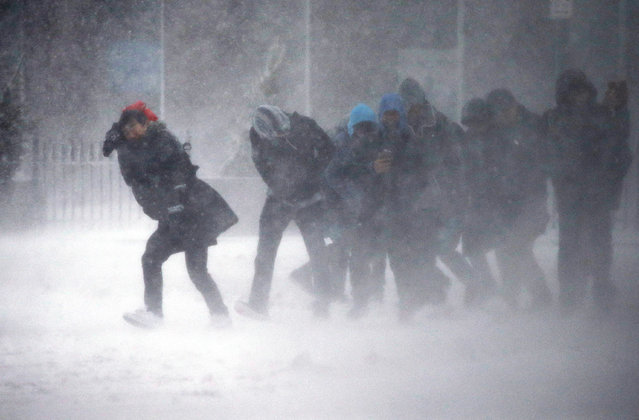 People struggle to walk in the blowing snow during a winter storm Tuesday, March 14, 2017, in Boston. (Photo by Michael Dwyer/AP Photo)