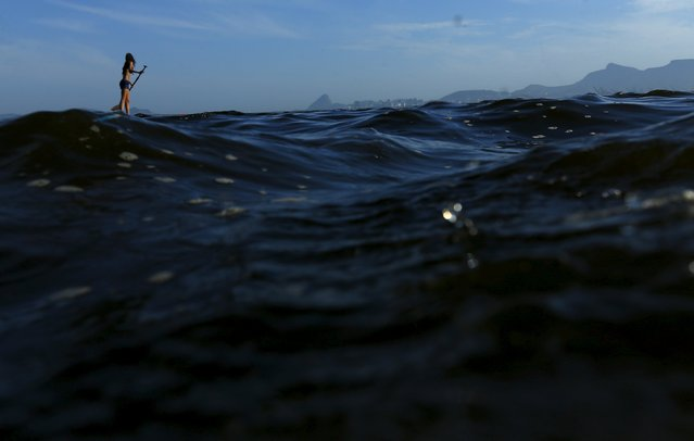 A girl paddles on her stand-up board on the waters of Guanabara bay at Bica beach in Rio de Janeiro Brazil, January 10, 2016. (Photo by Ricardo Moraes/Reuters)