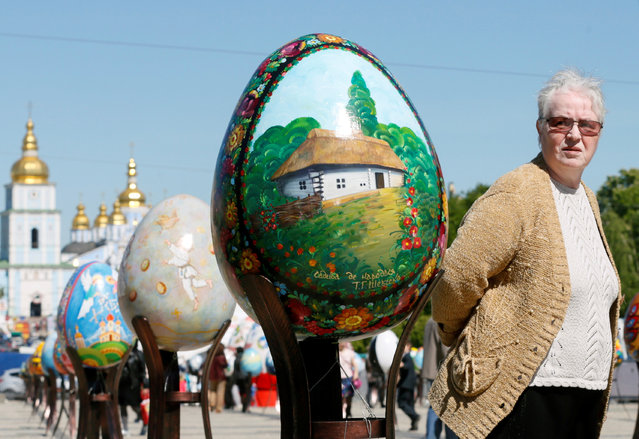 "A woman looks at traditional Ukrainian Easter eggs ""Pysanka"", installed as part of the upcoming celebrations of Easter, in central Kiev, Ukraine, April 29, 2016. A pysanka is a Ukrainian Easter egg, decorated with traditional Ukrainian folk designs using a wax-resist (batik) method. The word pysanka comes from the verb pysaty, ""to write"", as the designs are not painted on, but written with beeswax. Many other eastern European ethnic groups decorate eggs using wax resist for Easter. These include the Belarusians, Bulgarians, Croats, Czechs, Hungarians, Lithuanians, Poles, Romanians, Serbs, Slovaks, Slovenes and Sorbs. (Photo by Valentyn Ogirenko/Reuters)"