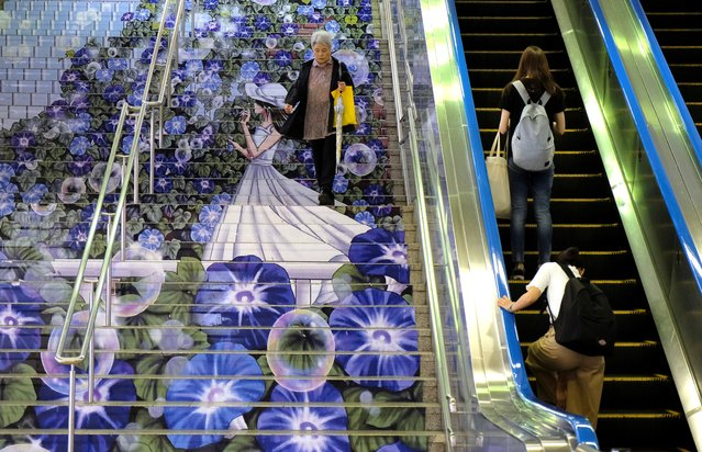 A commuter (L) walks down stairs adorned with artwork of a girl surrounded by morning glories at an entrance of the JR Kumagaya Station in Kumagaya, Saitama Prefecture on July 15, 2019. (Photo by Kazuhiro Nogi/AFP Photo)