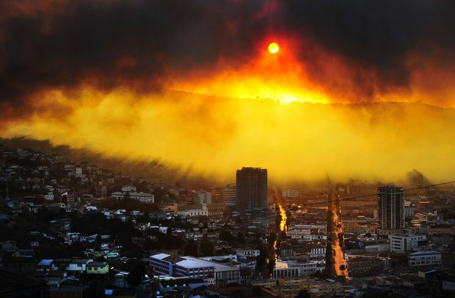 A general view shows a fire in Valparaiso, 110 km west of Santiago, Chile, on April 12, 2014. Authorities decreed a red alert for the area after the fire consumed more than 100 houses. (Photo by Alberto Miranda/AFP Photo)
