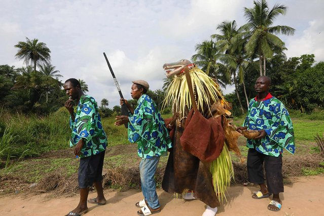 The men's secret hunting society members of Songo village begin their processional through town on December 7, 2018. Leading the group is Oninfara who blows a whistle to communicate to other members that the devil is coming out. Next in line is Oninbele who carries a gun for protection of the large masked animal devil walking behind him. Taking up the rear of the processional is Oninsaweh who uses herbs and a bowl called a calabash to fan spiritual medicine to protect the devil. (Photo by Lynn Rossi/AFP Photo)