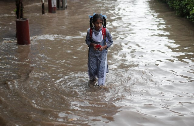 A schoolgirl wades through a flooded street after heavy rains in New Delhi, India, August 6, 2019. (Photo by Adnan Abidi/Reuters)