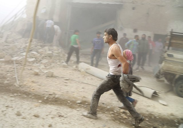 Civilians, who survived what activists said were barrel bombs dropped by forces loyal to Syria's President Bashar al-Assad, run in Aleppo's al-Shaar district April 24, 2014. (Photo by Ahmad Othman/Reuters)