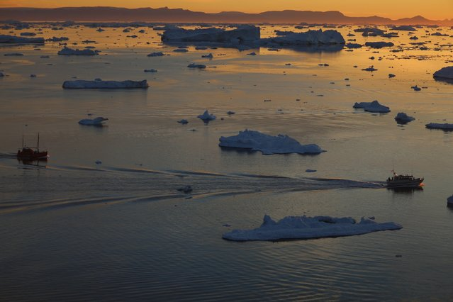 Ships are seen among the icebergs that broke off from the Jakobshavn Glacier as the sun reaches its lowest point of the day on July 23, 2013 in Ilulissat, Greenland. (Photo by Joe Raedle/Getty Images)