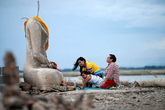 A family prays near the ruins of a headless Buddha statue, which has resurfaced in a dried-up dam due to drought, in Lopburi, Thailand on August 1, 2019. Thousands are flocking to see the Buddhist temple exposed after drought drove water levels to record lows in a dam reservoir where it had been submerged. (Photo by Soe Zeya Tun/Reuters)