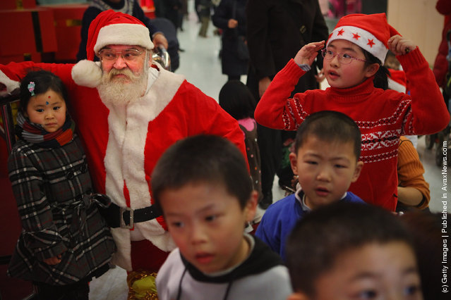 Santa stays with Chinese children at a shopping center on Christmas Eve