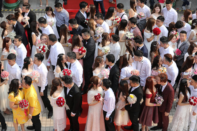 Newlywed couples kiss during a mass wedding in Kuala Lumpur, Malaysia, September 9, 2019. A mass wedding ceremony was held for 99 couples on the ninth day of the ninth month, considered an auspicious date, at a Chinese temple in the city. (Photo by Lim Huey Teng/Reuters)