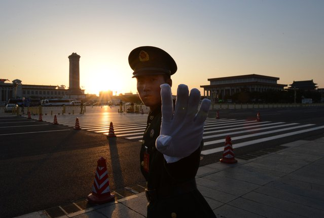 A Chinese paramilitary policeman reacts outside the opening session of the Chinese Communist Party's five-yearly Congress at the Great Hall of the People in Beijing on November 8, 2012. The week-long congress, held every five years, will end with a transition of power to Vice President Xi Jinping, who will govern for the coming decade amid growing pressure for reform of the communist regime's iron-clad grip on power. (Photo by Mark Ralston/AFP Photo)